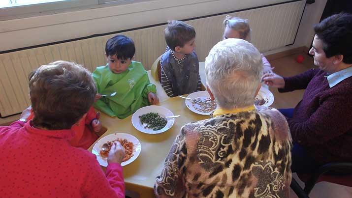 Amonas y aitonas del Centro de Día de Personas Mayores de Arrasate dan de comer a niñas y niños de Arizmendi